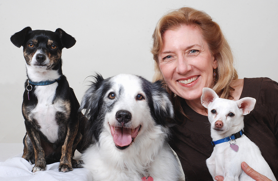 Smiling woman with three dogs, on white background; dogs which get along with other pets